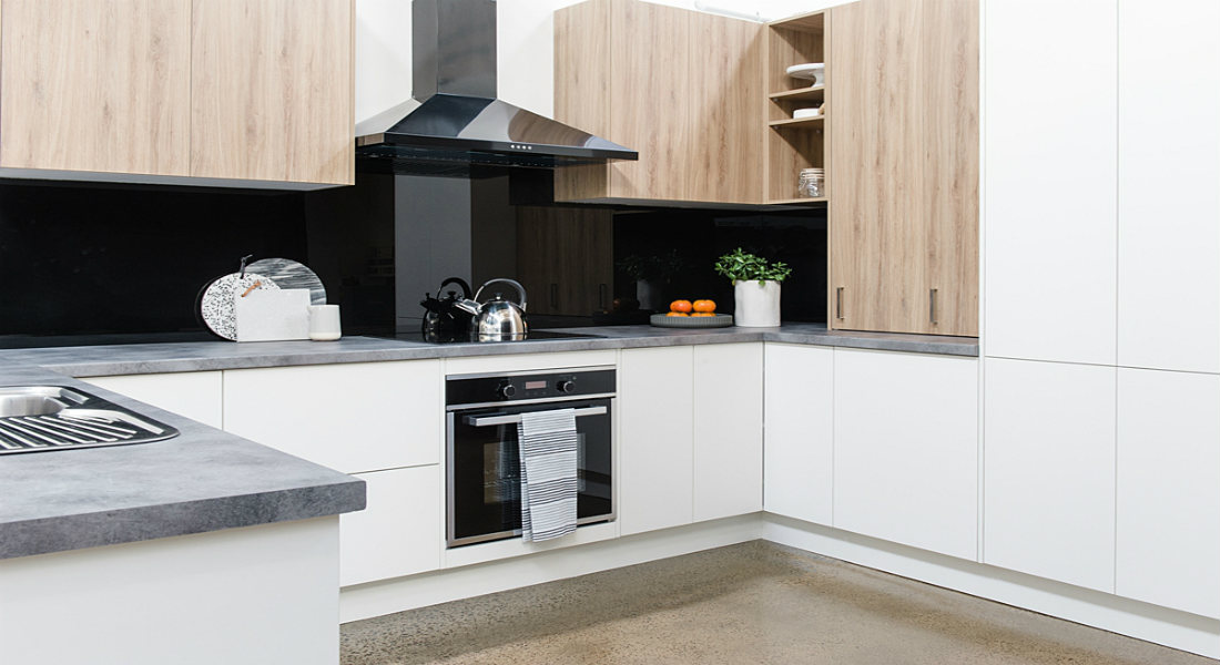 Kitchen with a black splashback and white cabinetry giving a contrast look