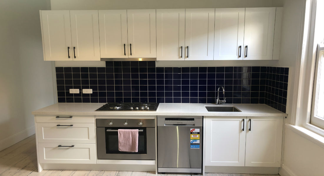 Kitchen with contrasting colours along with white cabinet and black tiled splashback