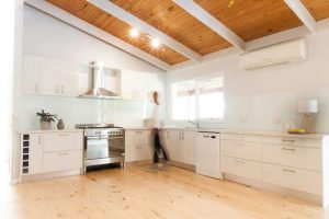 White cabinetry with timber racked ceiling