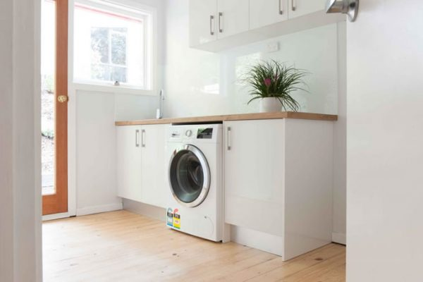 White laundry cabinetry with timber laminate benchtop