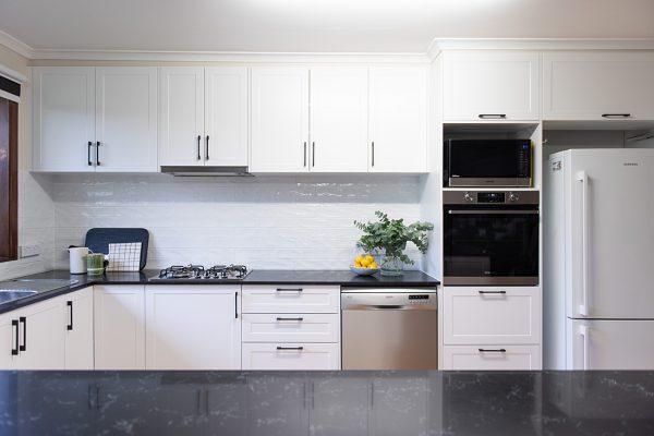 White kitchen with dark benchtops